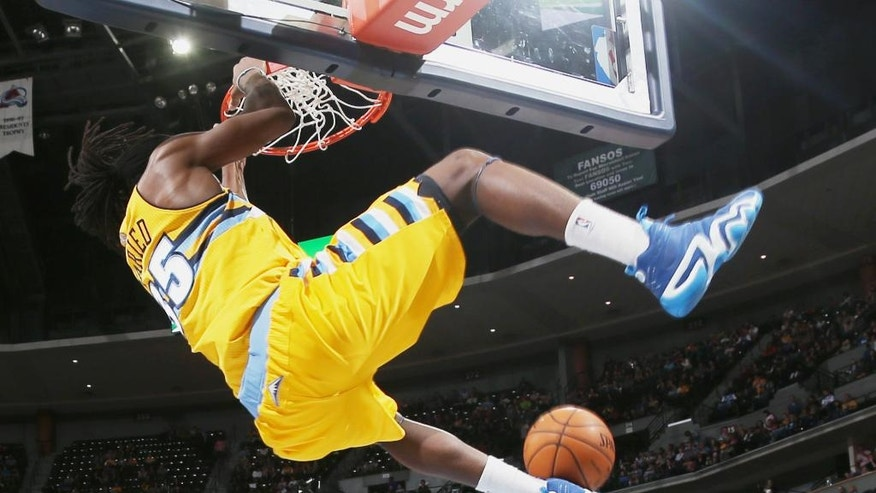 Denver Nuggets forward Kenneth Faried, top, hangs on the rim after dunking the ball for a basket over Utah Jazz forward Jeremy Evans in the first quarter of an NBA basketball game in Denver on Saturday, April 12, 2014. (AP Photo/David Zalubowski)