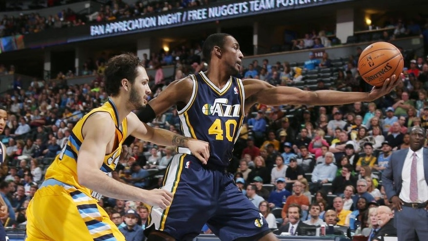 Utah Jazz forward Jeremy Evans, right, reaches out to pull in a loose ball as Denver Nuggets guard Evan Fournier, of France, covers in the first quarter of an NBA basketball game in Denver on Saturday, April 12, 2014. (AP Photo/David Zalubowski)