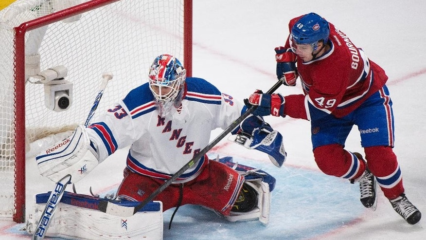New York Rangers goaltender Cam Talbot makes a save against Montreal Canadiens' Michael Bournival, right, during the third period of an NHL hockey game, Saturday, April 12, 2014, in Montreal. Montreal won 1-0 in overtime. (AP Photo/The Canadian Press, Graham Hughes)