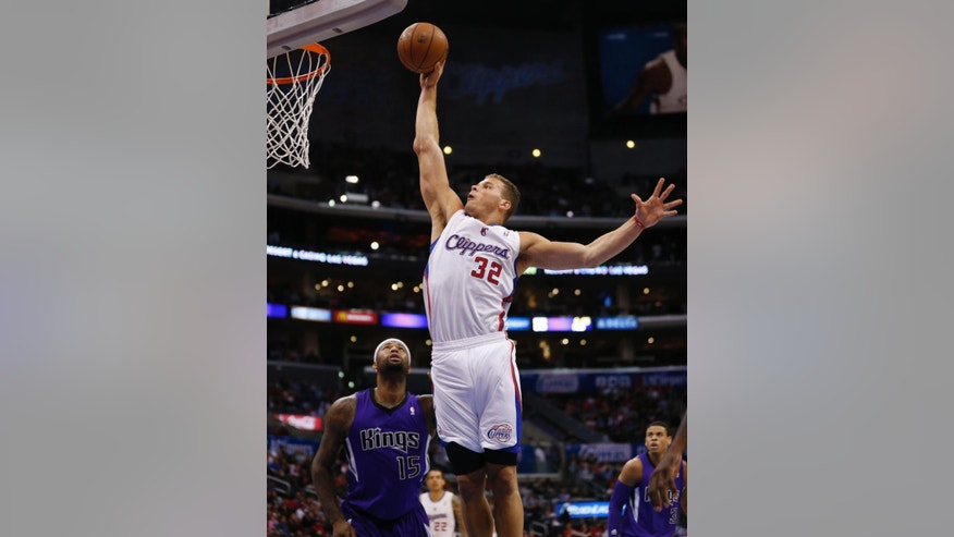 Los Angeles Clippers forward Blake Griffin dunks the ball over Sacramento Kings center DeMarcus Cousins during the first half of an NBA basketball game in Los Angeles, Sunday, April 12, 2014. (AP Photo/Danny Moloshok)