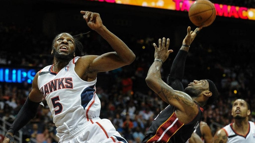 Miami Heat forward LeBron James, front right, is fouled under the basket by Atlanta Hawks forward DeMarre Carroll (5) during the first half of an NBA basketball game on Saturday, April 12, 2014, in Atlanta. (AP Photo/John Amis)