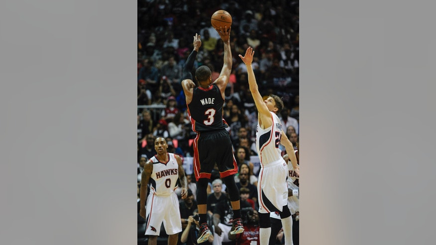 Miami Heat guard Dwyane Wade (3) makes a jump shot over the defense of Atlanta Hawks guard Kyle Korver (26) during the first half of an NBA basketball game on Saturday, April 12, 2014, in Atlanta. (AP Photo/John Amis)