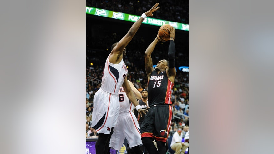 Miami Heat guard Mario Chalmers (15) shoots against the defense of Atlanta Hawks forward Elton Brand, left, during the first half of an NBA basketball game on Saturday, April 12, 2014, in Atlanta. (AP Photo/John Amis)