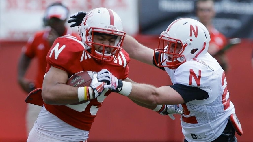 Nebraska running back Jordan Nelson, left, is pursued by cornerback Anthony Ridder during Nebraska's NCAA college spring football game in Lincoln, Neb., Saturday, April 12, 2014. (AP Photo/Nati Harnik)