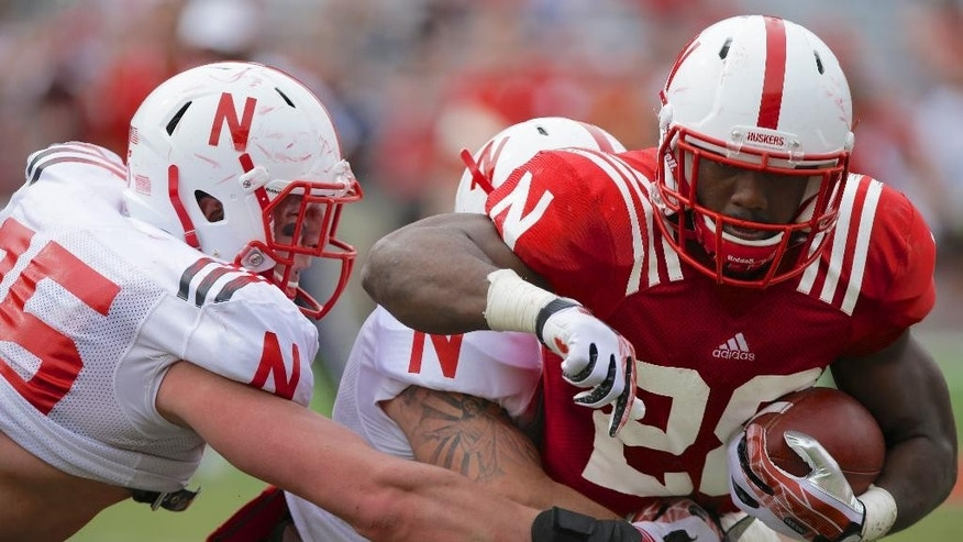Nebraska running back Adam Taylor, right, is tackled by defensive end Jack Gangwish during an NCAA college football spring game in Lincoln, Neb., Saturday, April 12, 2014. (AP Photo/Nati Harnik)