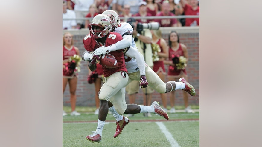 After making a long reception Jesus Wilson, left, of the garnet team has the ball knocked away by P.J. Williams of the gold team during the first half of a spring practice football game on Saturday, April 12, 2014, in Tallahassee, Fla.(AP Photo/Steve Cannon)
