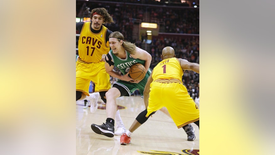 Boston Celtics' Kelly Olynyk (41) drives between Cleveland Cavaliers' Anderson Varejao (17), from Bazil, and Jarrett Jack (1) during the first quarter of an NBA basketball game Saturday, April 12, 2014, in Cleveland. (AP Photo/Tony Dejak)