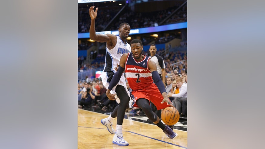 Washington Wizards guard John Wall (2) drives past Orlando Magic center Dewayne Dedmon during the first half of an NBA basketball game in Orlando, Fla., Friday, April 11, 2014. (AP Photo/Reinhold Matay)