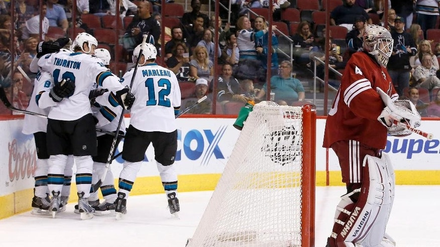 San Jose Sharks' Joe Pavelski (8) celebrates his goal against Phoenix Coyotes' Mark Visentin, right, with teammates, including Joe Thornton, second from left, and Patrick Marleau (12), during the first period of an NHL hockey game on Saturday, April 12, 2014, in Glendale, Ariz. (AP Photo/Ross D. Franklin)