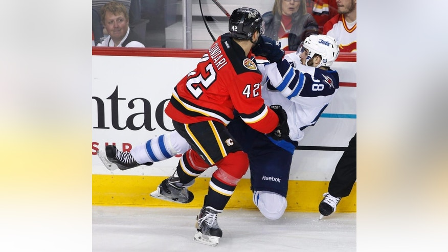 Winnipeg Jets' Eric O'Dell, right, takes a hit from Calgary Flames' Mark Cundari during second period NHL action in Calgary, Alberta, Friday, April 11, 2014. (AP Photo/The Canadian Press, Larry MacDougal)