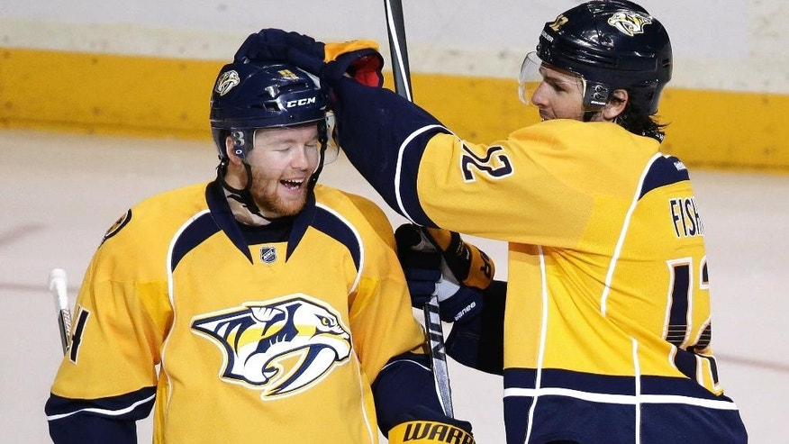 Nashville Predators defenseman Ryan Ellis, left, is congratulated by Mike Fisher after Ellis scored against the Chicago Blackhawks in the second period of an NHL hockey game Saturday, April 12, 2014, in Nashville, Tenn. (AP Photo/Mark Humphrey)