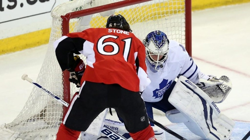 Ottawa Senators' Mark Stone (61) has the puck knocked away by Toronto Maple Leafs goaltender James Reimer during first-period NHL hockey game action in Ottawa, Ontario, Saturday, April 12, 2014. (AP Photo/The Canadian Press, Fred Chartrand)