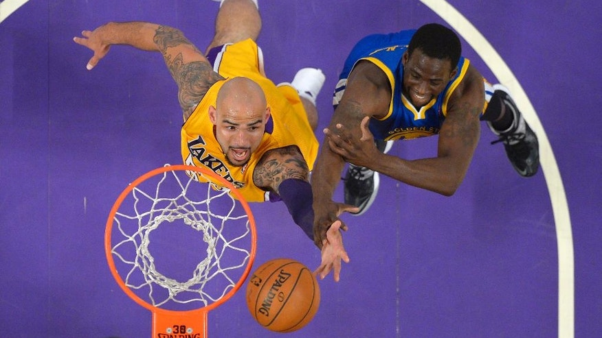 Los Angeles Lakers center Robert Sacre, left, shoots as Golden State Warriors forward Draymond Green defends during the first half of an NBA basketball game, Friday, April 11, 2014, in Los Angeles. (AP Photo/Mark J. Terrill)