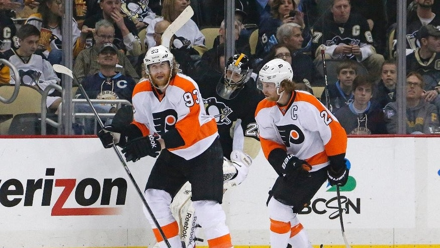Philadelphia Flyers' Jakub Voracek (93) celebrates his goal with teammate Claude Giroux (28) as Pittsburgh Penguins goalie Marc-Andre Fleury (29), rear center, look son during the second period of an NHL hockey game in Pittsburgh, Saturday, April 12, 2014. It was the second goal of the game for Voracek. (AP Photo/Gene J. Puskar)