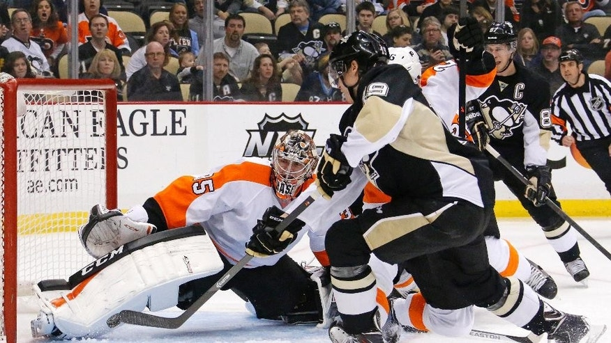 Pittsburgh Penguins' Beau Bennett (19) can't get a shot past Philadelphia Flyers goalie Steve Mason (35) during the second period of an NHL hockey game in Pittsburgh, Saturday, April 12, 2014. (AP Photo/Gene J. Puskar)