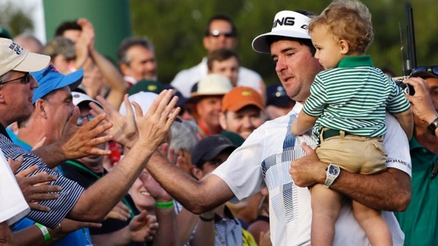 April 13, 2014: Bubba Watson, carrying his son Caleb, is congratulated by spectators after winning the Masters golf tournament in Augusta, Ga.