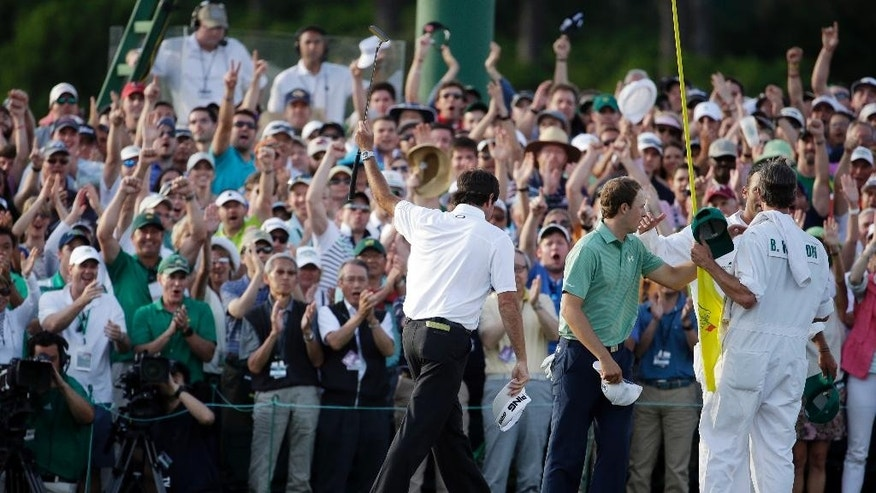 Spectators applaud Bubba Watson, left,  after winning the Masters golf tournament Sunday, April 13, 2014, in Augusta, Ga. Second right is Jordan Spieth and their caddies. (AP Photo/Darron Cummings)