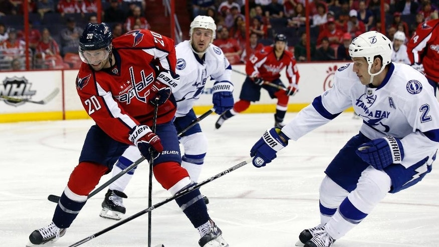 Washington Capitals right wing Troy Brouwer (20) goes for the puck with Tampa Bay Lightning defenseman Eric Brewer (2) in the second period of an NHL hockey game on Sunday, April 13, 2014, in Washington. (AP Photo/Alex Brandon)