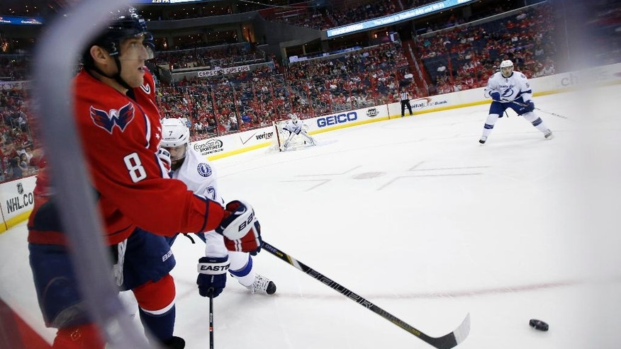 Washington Capitals right wing Alex Ovechkin (8), from Russia, passes in front of Tampa Bay Lightning defenseman Radko Gudas (7), from the Czech Republic, in the first period of an NHL hockey game on Sunday, April 13, 2014, in Washington. (AP Photo/Alex Brandon)