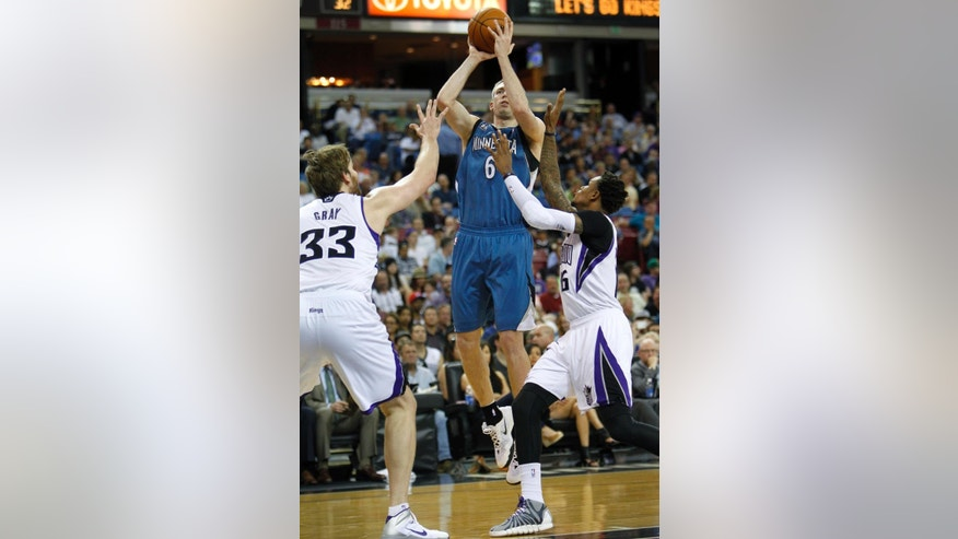 Minnesota Timberwolves forward Robbie Hummel (6) shoots over Sacramento Kings defenders Aaron Gray (33) and Ben McLemore (16) during the first half of an NBA basketball game in Sacramento, Calif., on Sunday, April 13, 2014.(AP Photo/Steve Yeater)