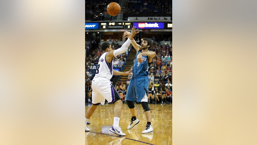 Minnesota Timberwolves guard Ricky Rubio (9) passes the ball over Sacramento Kings defender Ray McCallum during the first half of an NBA basketball game in Sacramento, Calif., on Sunday, April 13, 2014.(AP Photo/Steve Yeater)