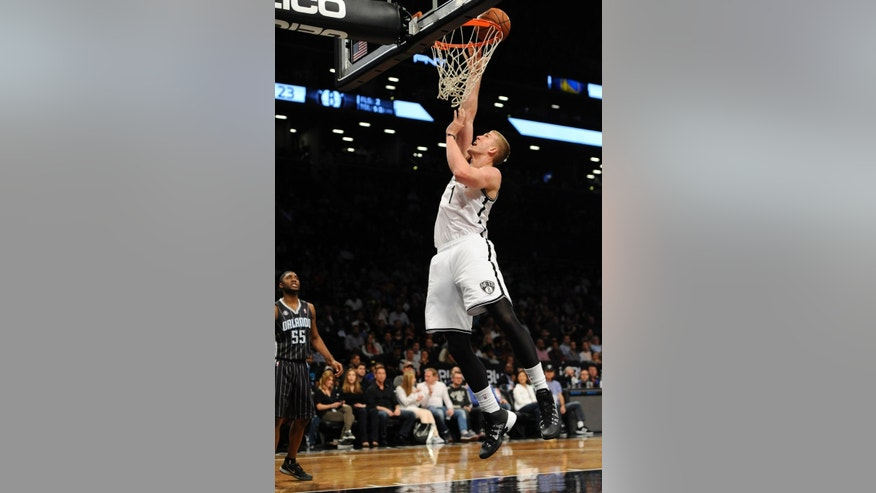 Brooklyn Nets' Mason Plumlee (1) releases a shot as Orlando Magic's E'Twaun Moore (55) watches during the first half of an NBA basketball game Sunday, April 13, 2014, in New York. The Nets won 97-88. (AP Photo/Kathy Kmonicek)