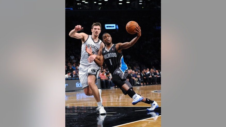 Brooklyn Nets' Mirza Teletovic (33) defends Orlando Magic's Doron Lamb (1) duirng the second half of an NBA basketball game Sunday, April 13, 2014, in New York. The Nets won 97-88. (AP Photo/Kathy Kmonicek)