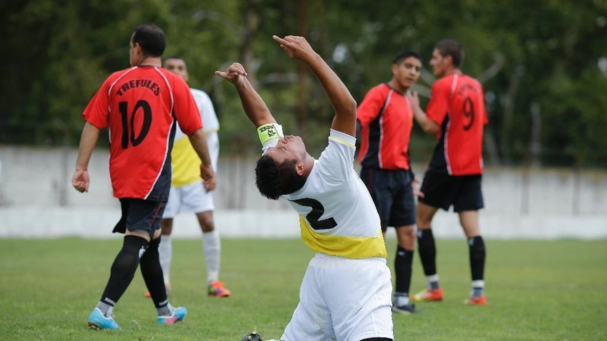 "Ernesto Ortiz, from the new semi-professional soccer team ""Papa Francisco,"" or Pope Francis, kneels and gestures to the sky after missing a chance to score against Trefules during their debut game in Lujan, Argentina, Saturday, April 12, 2014. The team named in honor of the Argentine pontiff chose the colors of the Vatican flag for their uniforms. (AP Photo/Victor R. Caivano)"