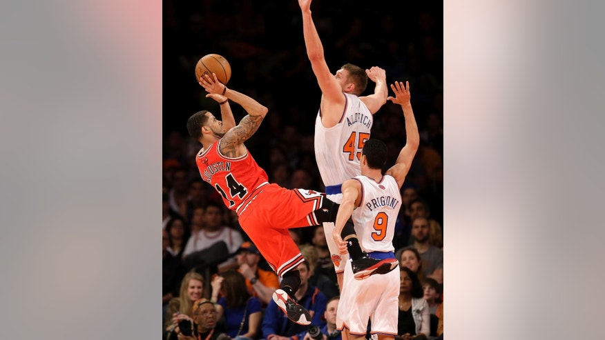 Chicago Bulls' D.J. Augustin, left, is fouled by New York Knicks' Pablo Prigioni, right, while Cole Aldrich also defends during the first half of the NBA basketball game, Sunday, April 13, 2014, in New York. (AP Photo/Seth Wenig)