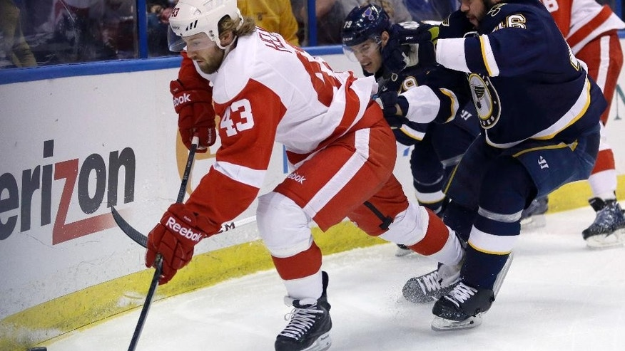 Detroit Red Wings' Darren Helm, left, reaches for a loose puck as St. Louis Blues' Adam Cracknell, center rear, and Roman Polak, of the Czech Republic, defend during the first period of an NHL hockey game Sunday, April 13, 2014, in St. Louis. (AP Photo/Jeff Roberson)