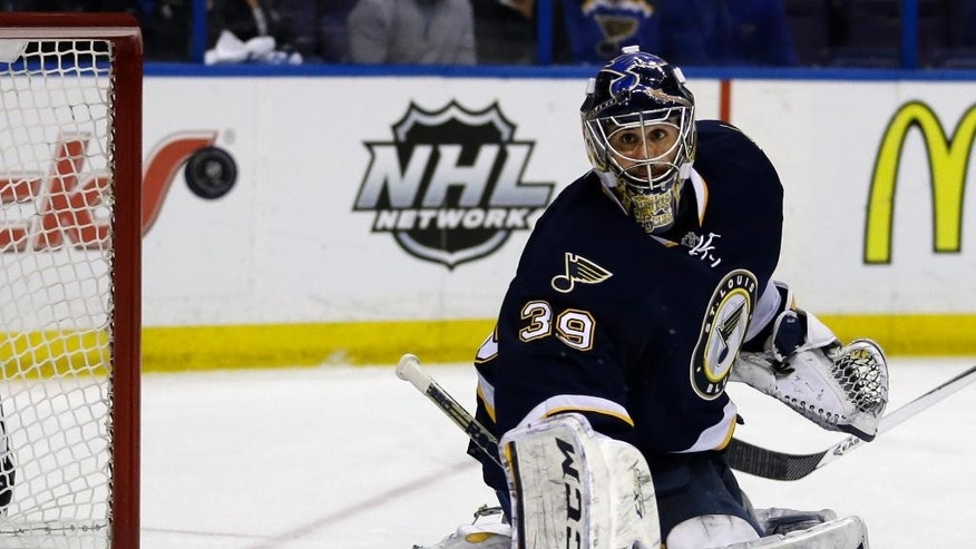 St. Louis Blues goalie Ryan Miller watches as a puck sails by during the first period of an NHL hockey game against the Detroit Red Wings on Sunday, April 13, 2014, in St. Louis. (AP Photo/Jeff Roberson)