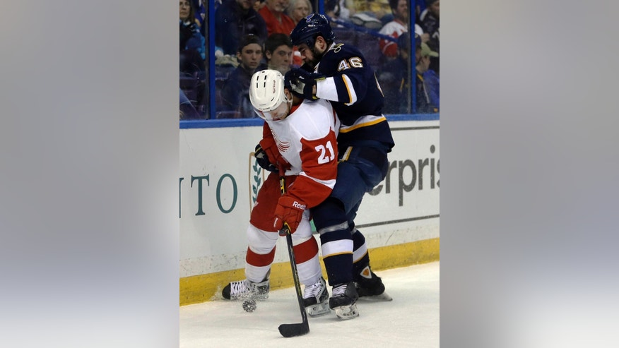 Detroit Red Wings' Tomas Tatar, left, of Slovakia, and St. Louis Blues' Roman Polak, of the Czech Republic, vie for a loose puck during the first period of an NHL hockey game Sunday, April 13, 2014, in St. Louis. (AP Photo/Jeff Roberson)
