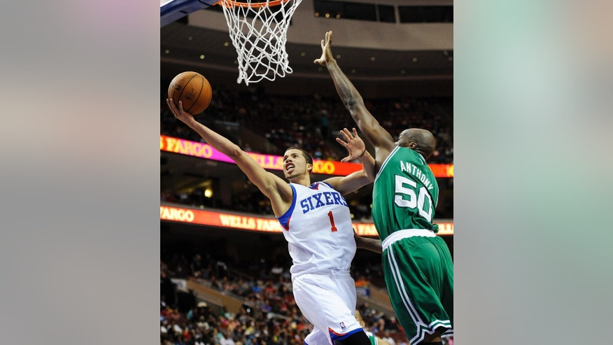 Philadelphia 76ers' Michael Carter-Williams (1) drives to the basket past Boston Celtics' Joel Anthony (50) during the second half of an NBA basketball game on Monday, April 14, 2014, in Philadelphia. The 76ers won 113-108. (AP Photo/Michael Perez)