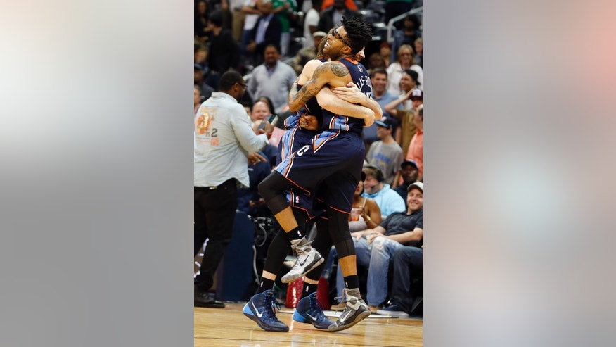 Charlotte Bobcats guard Chris Douglas-Roberts, right, embraces teammate Josh McRoberts (11) after hitting the game-winning shot as time expired  to defeat the Atlanta Hawks 95-93 in an NBA basketball game Monday, April 14, 2014 in Atlanta.  (AP Photo/John Bazemore)