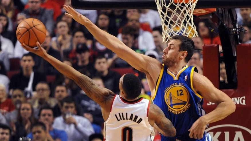Portland Trail Blazers guard Damian Lillard (0) drives to the basket on Golden State Warriors center Andrew Bogut (12) during the first half of an NBA basketball game in Portland, Ore., Sunday, April 13, 2014. (AP Photo/Steve Dykes)