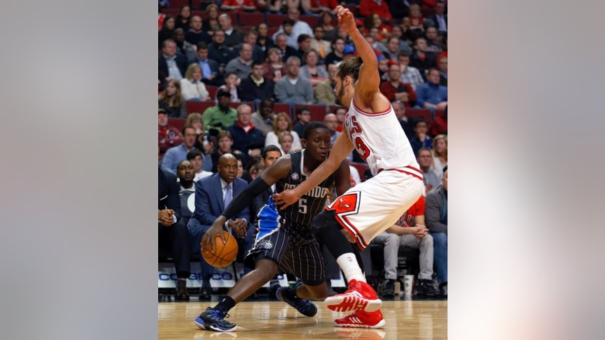 Orlando Magic guard Victor Oladipo, left, is guarded by Chicago Bulls center Joakim Noah, right, during the first half of an NBA basketball game Monday, April 14, 2014, in Chicago.  (AP Photo/Jeff Haynes)