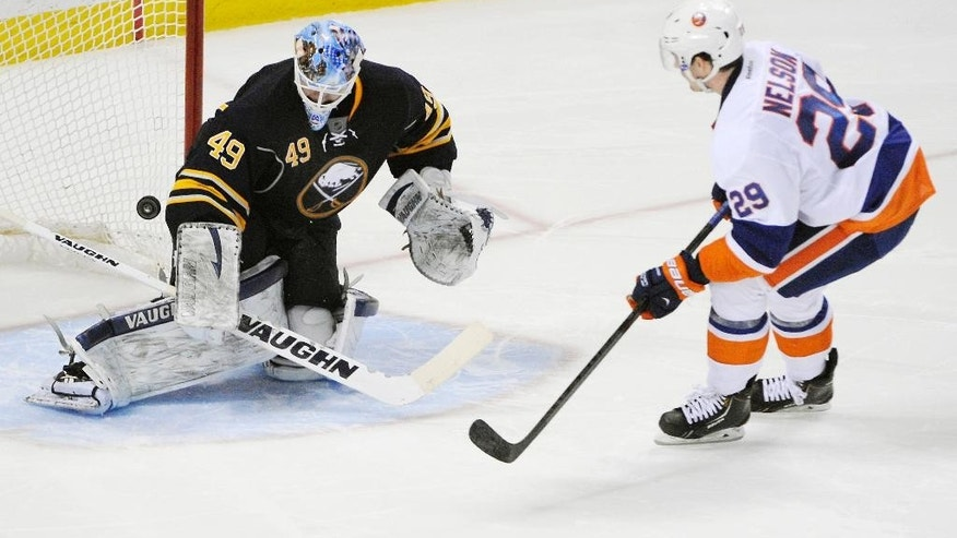 Buffalo Sabres goaltender Connor Knapp (49) gets beat as New York Islanders  center Brock Nelson (29) scores the game winning goal during the team shootout of an NHL hockey game in Buffalo, N.Y., Sunday April 13, 2014. New York won 4-3. (AP Photo/Gary Wiepert)