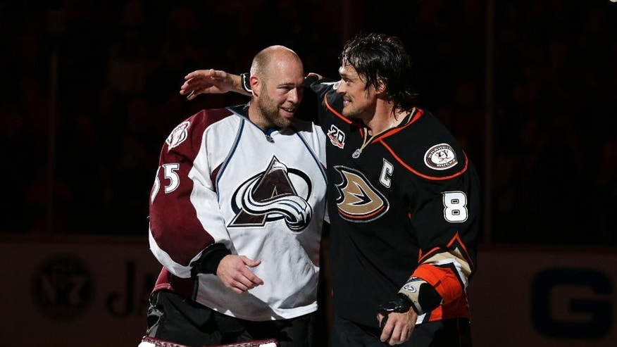Anaheim Ducks' Teemu Selanne, right, of Finland, and Colorado Avalanche goalie Jean-Sebastien Giguere, who plan to retire after the season, hug as they are honored after an NHL hockey game on Sunday, April 13, 2014, in Anaheim, Calif. The Ducks won 3-2 in overtime. (AP Photo/Jae C. Hong)