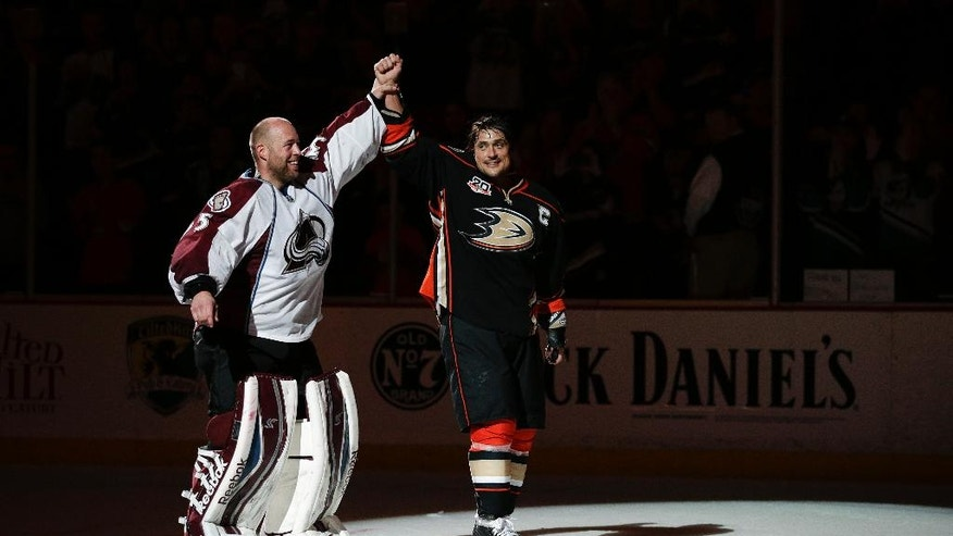 Anaheim Ducks' Teemu Selanne, right, of Finland, and Colorado Avalanche goalie Jean-Sebastien Giguere, who plan to retire after the season, skate on the ice as they are honored after an NHL hockey game on Sunday, April 13, 2014, in Anaheim, Calif. The Ducks won 3-2 in overtime. (AP Photo/Jae C. Hong)