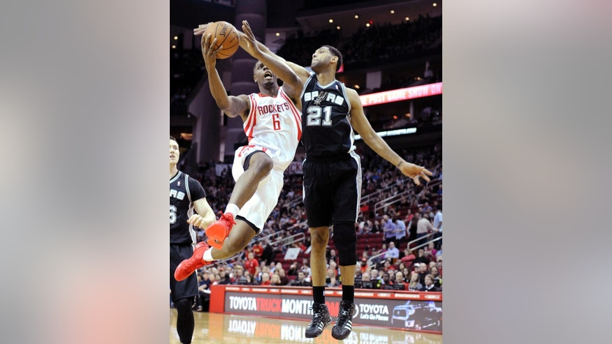 San Antonio Spurs' Tim Duncan (21) tries to block a shot by Houston Rockets' Terrence Jones (6) in the first half of an NBA basketball game Monday, April 14, 2014, in Houston. (AP Photo/Pat Sullivan)