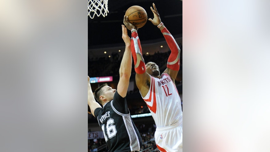 San Antonio Spurs' Aron Baynes (16) tries to block a shot by Houston Rockets' Dwight Howard (12) in the first half of an NBA basketball game Monday, April 14, 2014, in Houston. (AP Photo/Pat Sullivan)