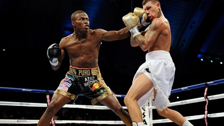"""ATLANTIC CITY, NJ - OCTOBER 26:  """"Kid Chocolate"""" Peter Quillin punches Gabriel Rosado during their middleweight fight in Boardwalk Hall Arena on October 26, 2013 in Atlantic City, New Jersey.  (Photo by Maddie Meyer/Getty Images)"""