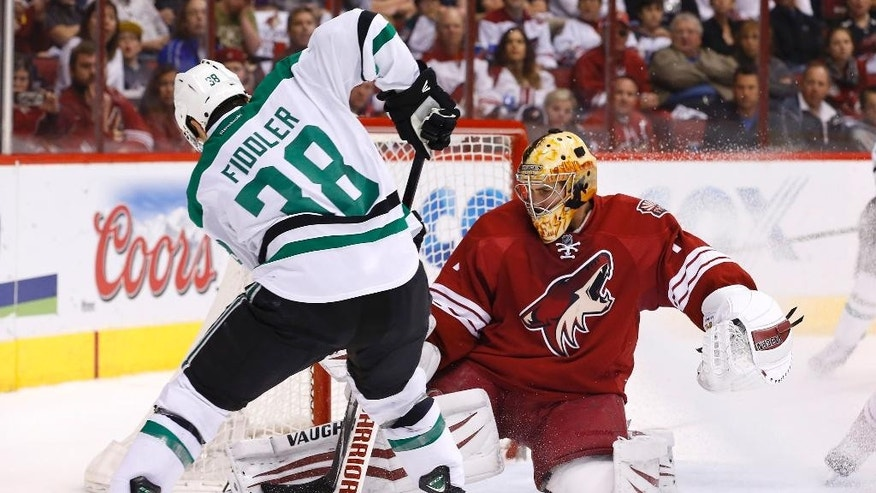 Phoenix Coyotes' Thomas Greiss, right, of Germany, makes a save on a shot by Dallas Stars' Vernon Fiddler (38) during the second period of an NHL hockey game on Sunday, April 13, 2014, in Glendale, Ariz.  The Coyotes defeated the Stars 2-1. (AP Photo/Ross D. Franklin)