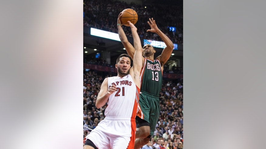 Milwaukee Bucks' Ramon Sessions, right, is fouled by Toronto Raptors' Greivis Vasquez during first half NBA basketball action in Toronto on Monday, April 14, 2014.   (AP Photo/The Canadian Press, Chris Young)