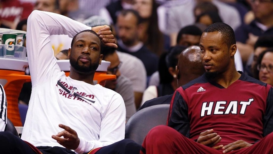 Miami Heat guard Dwyane Wade, left, and forward Rashard Lewis rest on the bench in the second half of an NBA basketball game against the Washington Wizards, Monday, April 14, 2014, in Washington. The Wizards won 114-93. (AP Photo/Alex Brandon)