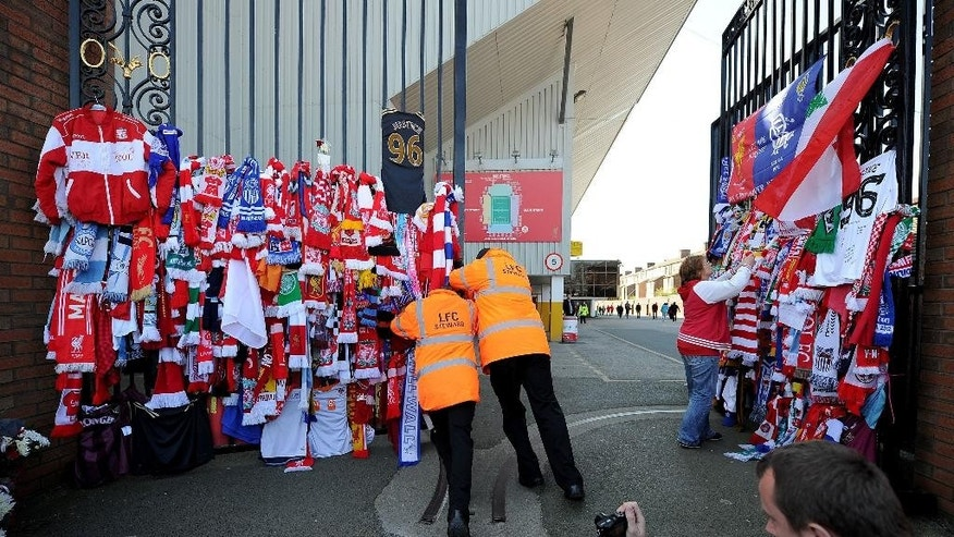 Stewards open the Shankly Gates at Anfield, Liverpool, England, before the Hillsborough 25th Anniversary Memorial Service, Tuesday April 15, 2014. About 30,000 people, including Liverpool players past and present, are expected to attend a memorial service at Anfield marking the 25th anniversary of the Hillsborough Stadium disaster that killed 96 Liverpool fans. Brendan Rodgers and Roberto Martinez, the managers of Liverpool and Everton, will deliver readings as Merseyside unites to remember those who died in Britain's worst sports tragedy. (AP Photo/PA, Martin Rickett)  UNITED KINGDOM OUT  NO SALES  NO ARCHIVE