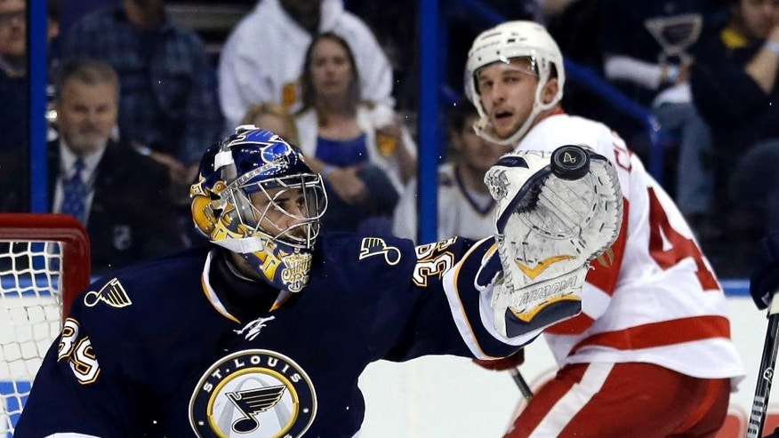 St. Louis Blues goalie Ryan Miller, left, grabs a puck as Detroit Red Wings' Luke Glendening watches during the third period of an NHL hockey game Sunday, April 13, 2014, in St. Louis. The Red Wings won 3-0. (AP Photo/Jeff Roberson)