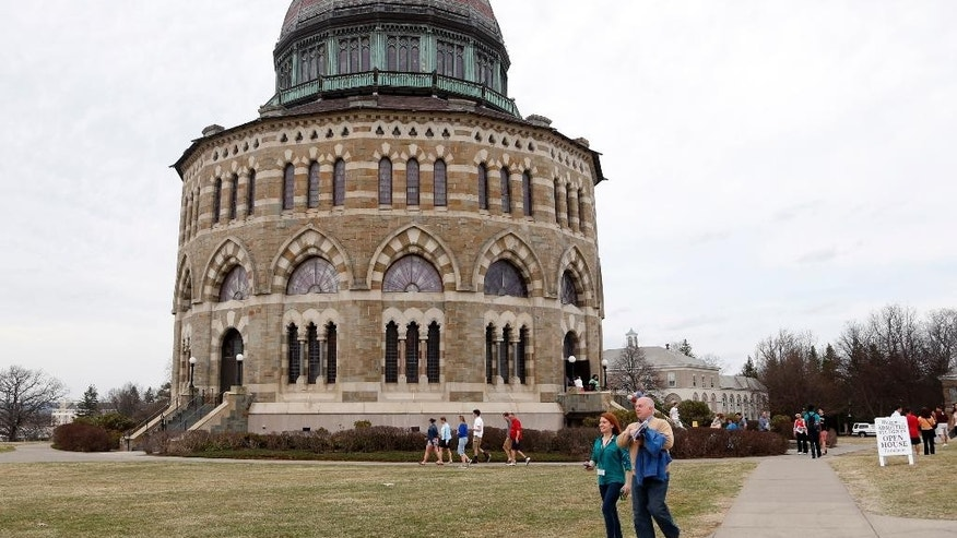 People walk by the Nott Memorial at Union College on Monday, April 14, 2014, in Schenectady, N.Y. Tiny Union, enrollment 2,200, defeated Minnesota, enrollment 48,000, Saturday for its first NCAA hockey title. (AP Photo/Mike Groll)