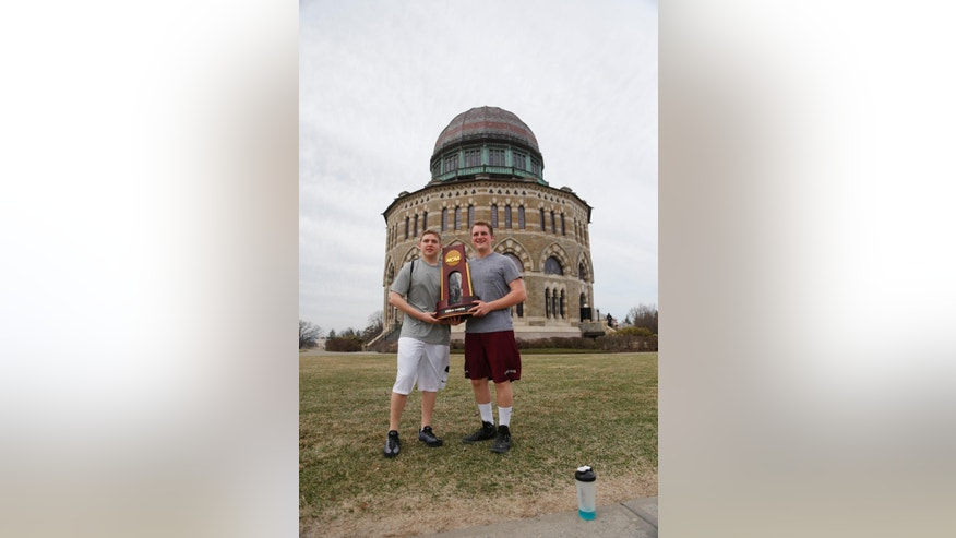 Freshmen Adam Appelbaum of Boston, left, and Liam Glennon of Schenectady, N.Y., pose with the NCAA men's hockey trophy won by Union College, in front of the Nott Memorial at Union on Monday, April 14, 2014, in Schenectady. Tiny Union, enrollment 2,200, defeated Minnesota, enrollment 48,000, Saturday for its first NCAA hockey title. (AP Photo/Mike Groll)