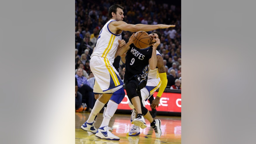 FILE - IN this Jan. 24, 2014, file photo, Golden State Warriors' Andrew Bogut, left, blocks Minnesota Timberwolves' Ricky Rubio during an NBA basketball game in Oakland, Calif. The Warriors will likely be without Bogut when they begin the playoffs this weekend. The loss of Bogut, who has a fractured right rib, leaves the Warriors without their best interior defender. (AP Photo/Ben Margot, File)